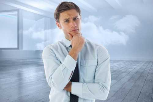 Thinking businessman with hand on chin against room with holographic cloud
