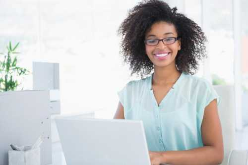 Happy hipster businesswoman working on laptop in her office